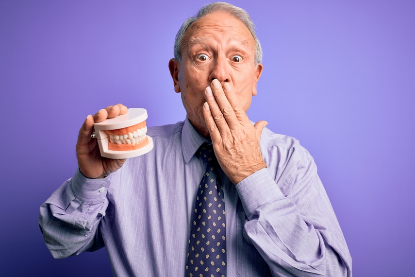 older man holding dentures with hand over mouth